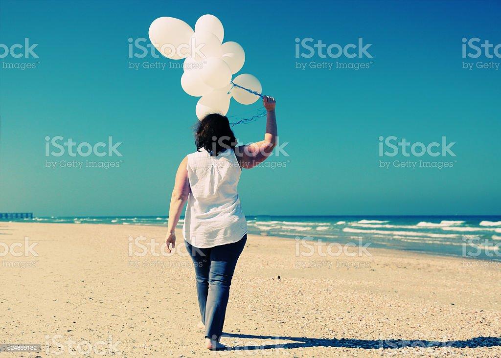 woman holding white balloons stock photo