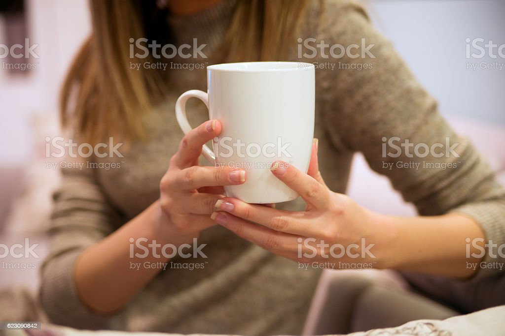 Woman holding white cup of coffee or tea stock photo
