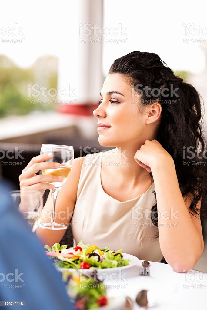 Woman Holding Wineglass While Looking Away At Restaurant Table royalty-free stock photo