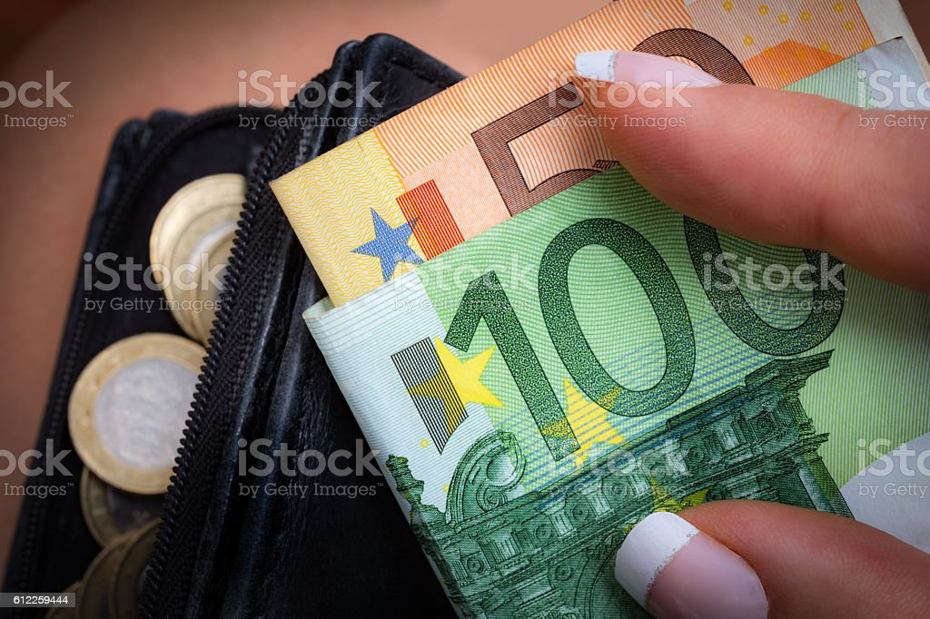 Woman holds 150 euro notes and wallet with  euros stock photo