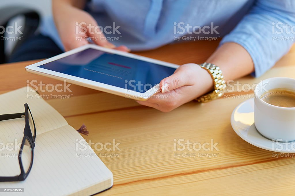 Woman holds a tablet with online banking stock photo