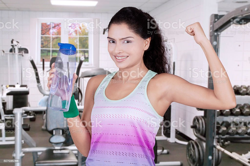 Woman holds beverage at gym stock photo