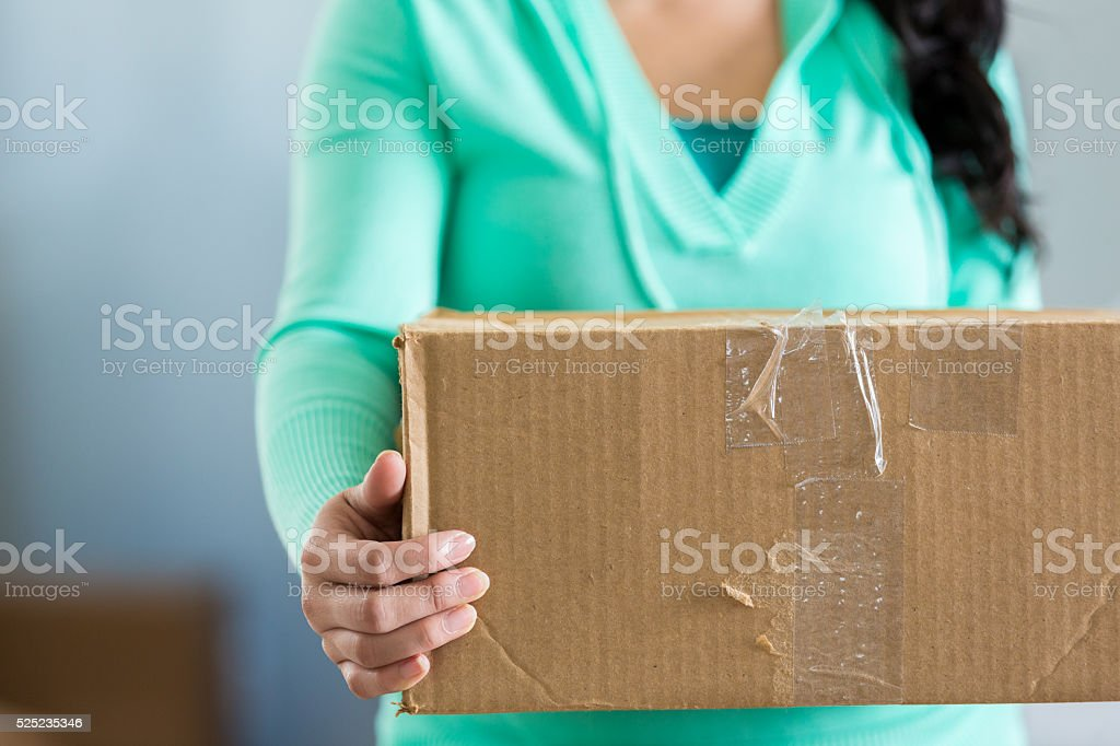 Woman holds cardboard box stock photo