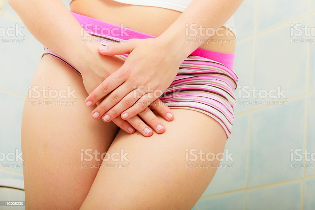 woman holds hands over her genital stock photo