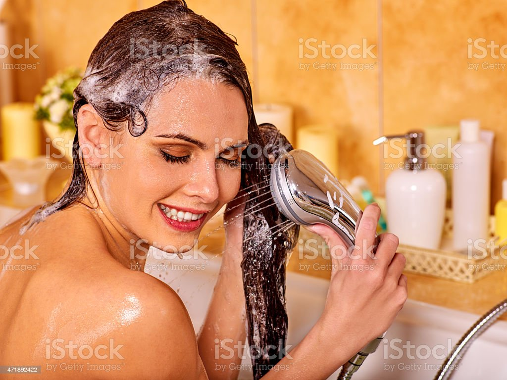 A woman holds her black hair while washing in the bathroom  stock photo