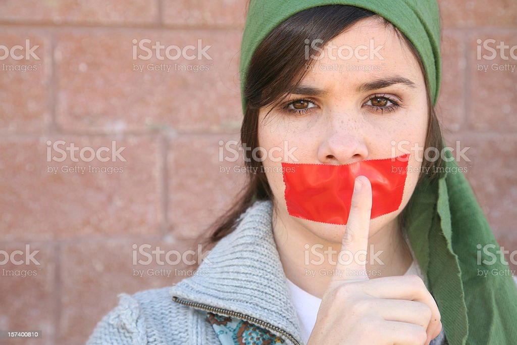 Woman Holds Her Finger To Mouth With Red Tape stock photo