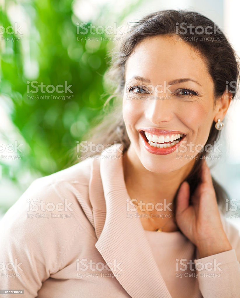 Woman holds her hair to her neck while smiling royalty-free stock photo