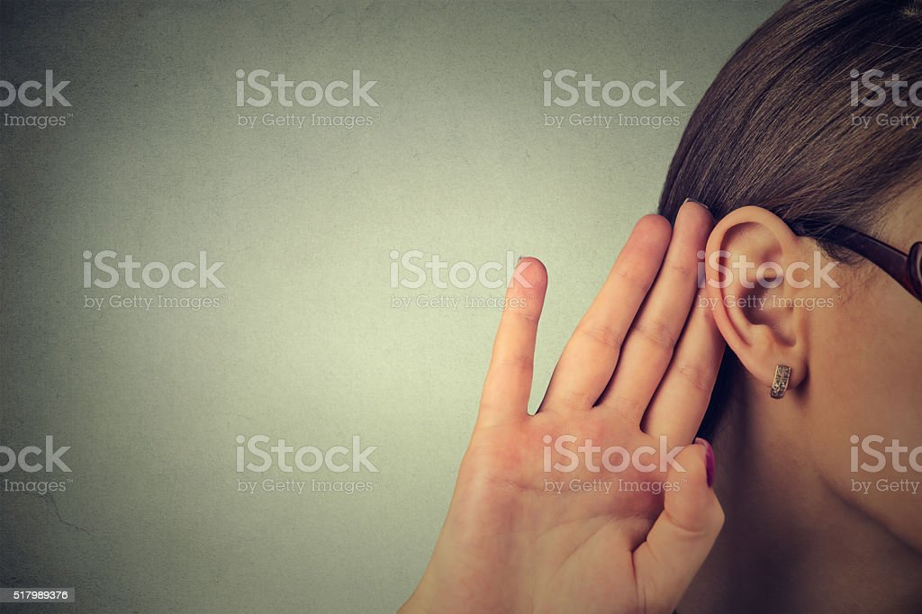 Woman holds her hand near ear and listens carefully stock photo