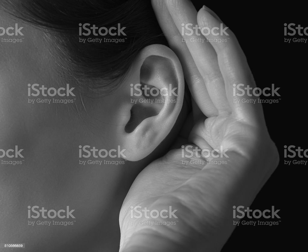 Woman holds her hand near ear stock photo