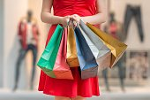 Woman holds many colorful shopping bags in hands.