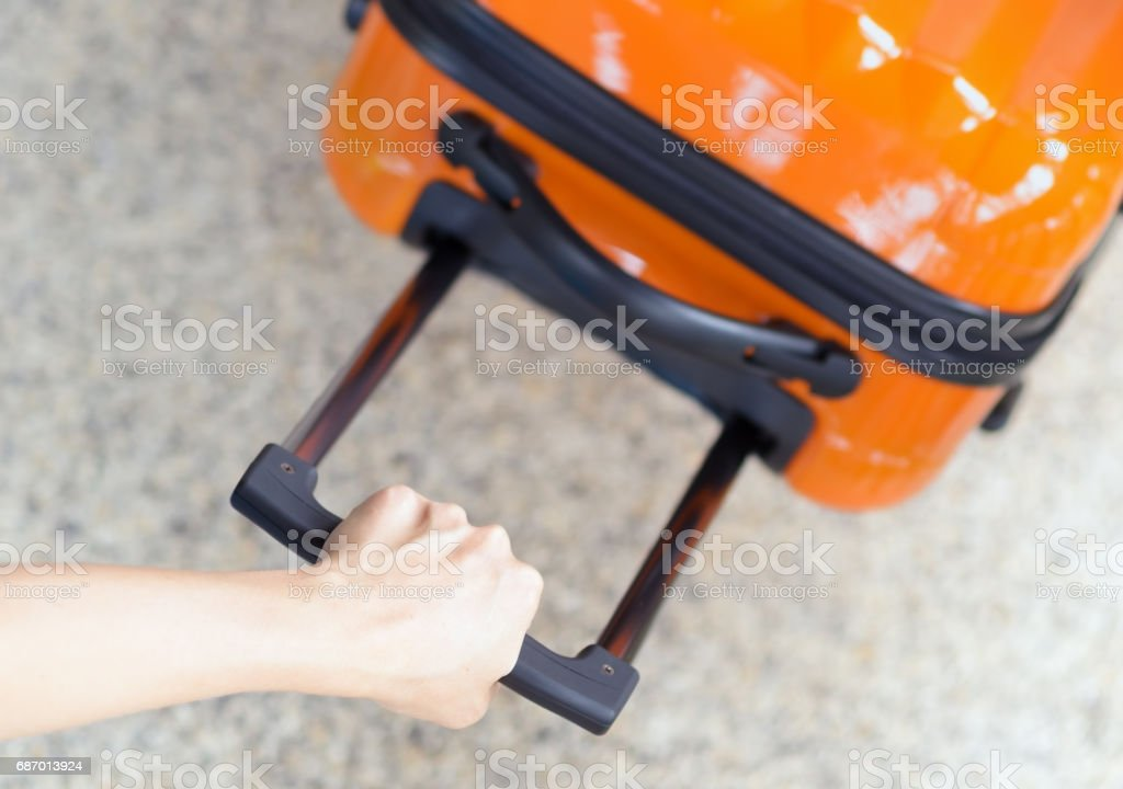 Woman holds orange suitcase in hand stock photo