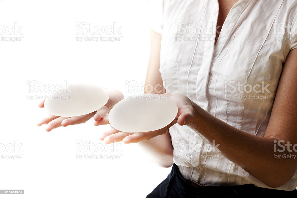 Woman holds out two silicone breast implants on her palms stock photo