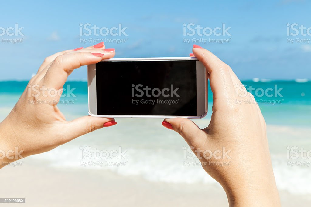 Woman holds phone for taking beach photo stock photo