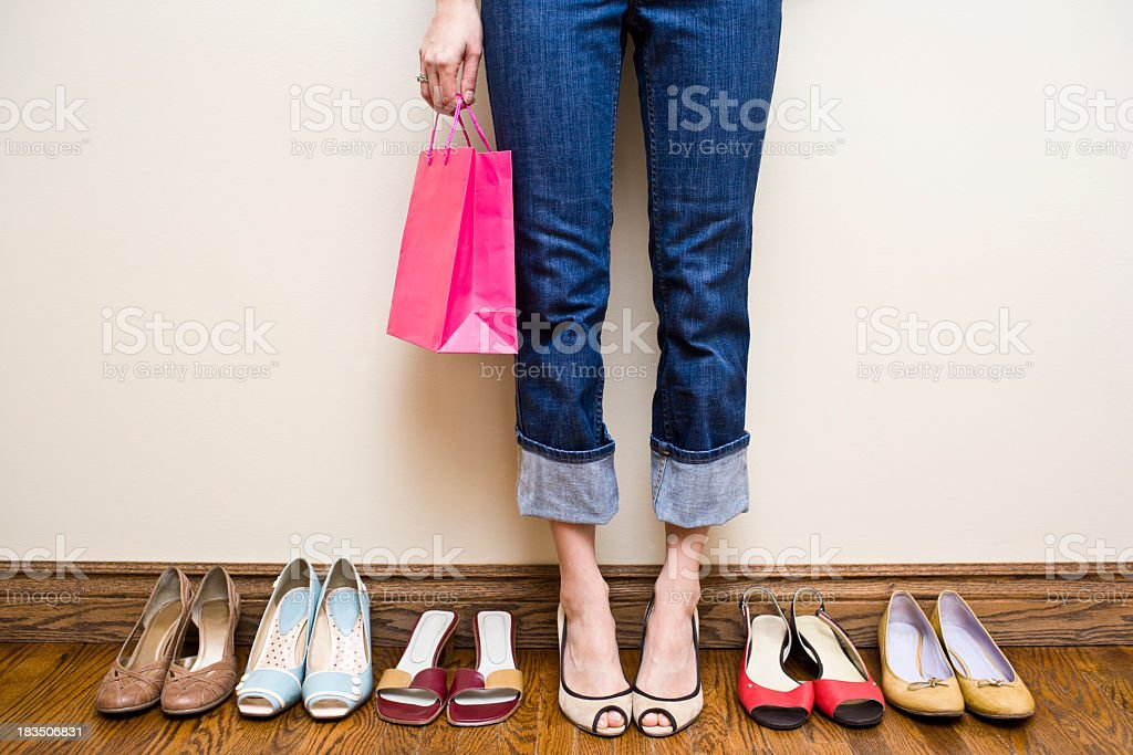 Woman holds shopping bag with many shoes showing Shoe Addiction royalty-free stock photo