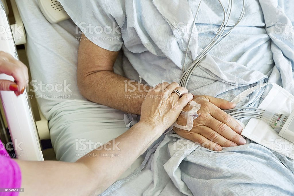 Woman holds the hand of her sick husband stock photo