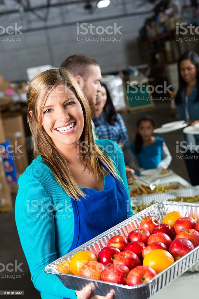 Woman holds tray of tresh fruit in soup kitchen stock photo
