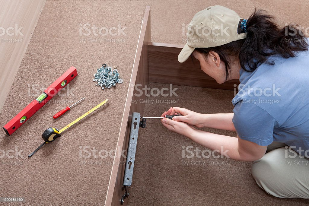 Woman housewife putting together assemble bed frame, using hand tools. stock photo