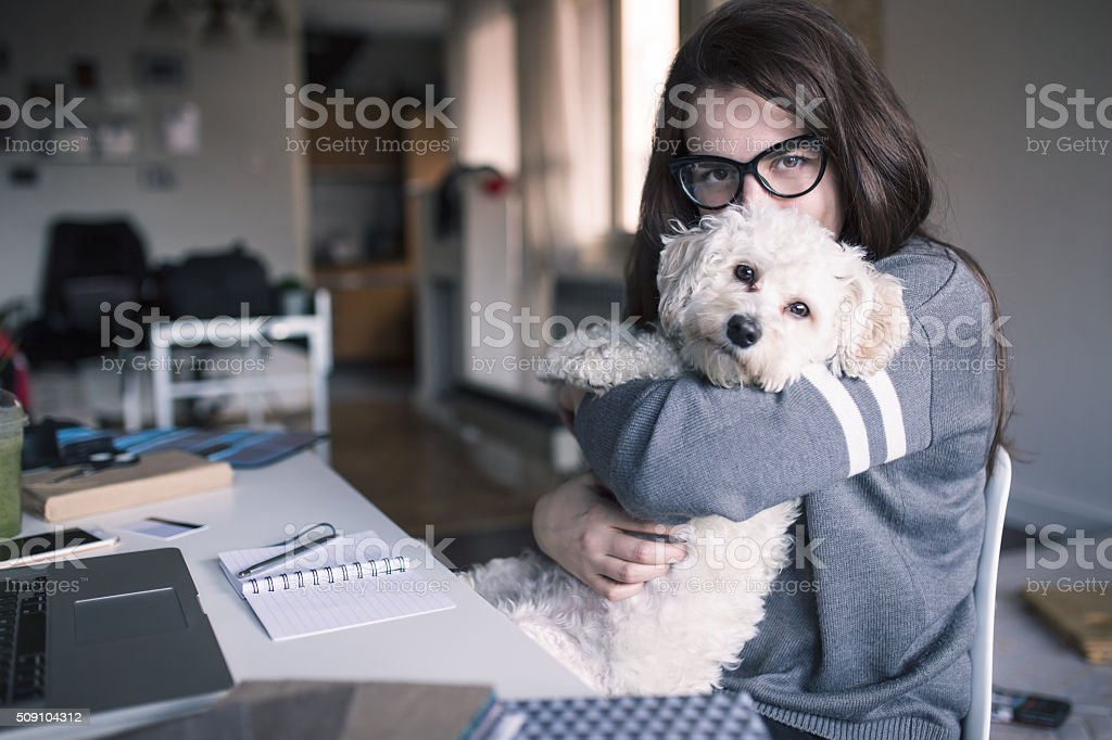 Woman hugging and kissing her dog stock photo