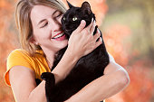 Woman Hugging Her Black Cat On Beautiful Fall Day
