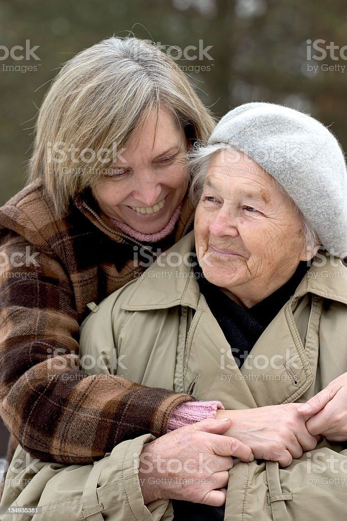 Woman hugging her elderly woman outside in the winter royalty-free stock photo