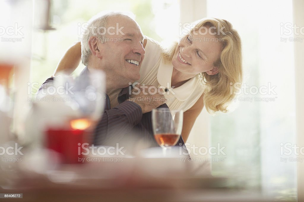 Woman hugging husband at dinner table royalty-free stock photo