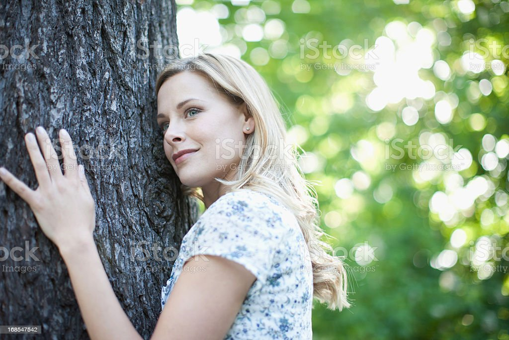 Woman hugging tree outdoors stock photo