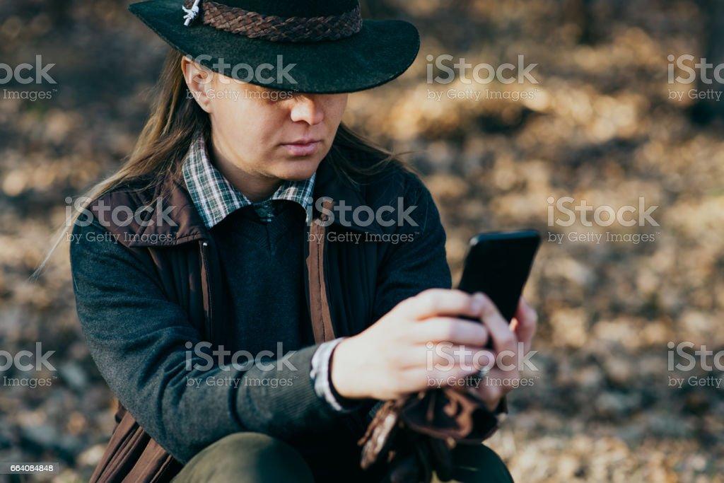 woman hunter using phone stock photo