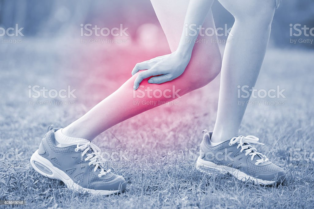 woman hurt leg in park stock photo