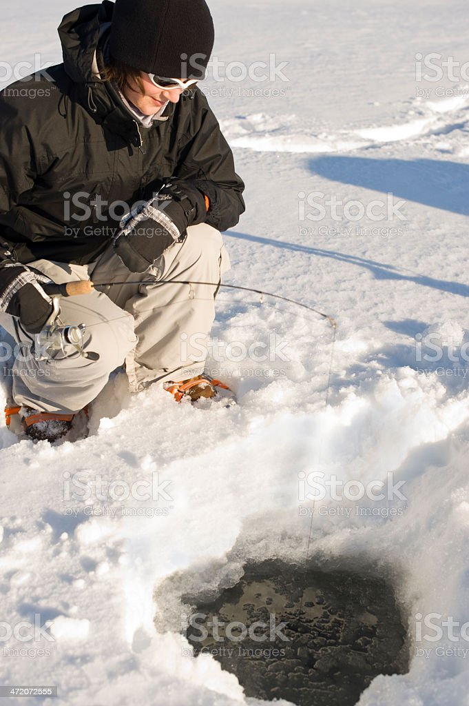 Woman Ice Fishing on Great Slave Lake in Canada's Arctic. stock photo