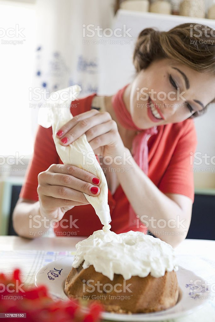 Woman icing a cake in kitchen royalty-free stock photo
