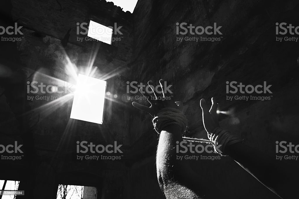 woman imprisoned stretches hands towards the light stock photo