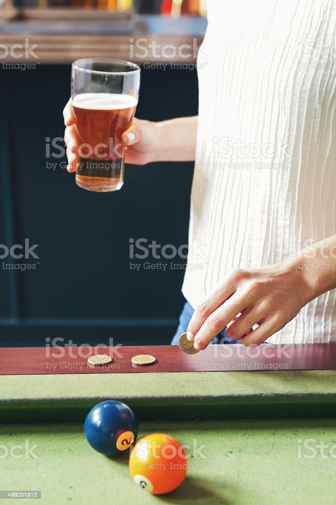 Woman in a bar putting dollar coin on pool table stock photo