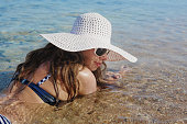 woman in a big white hat is in water of
