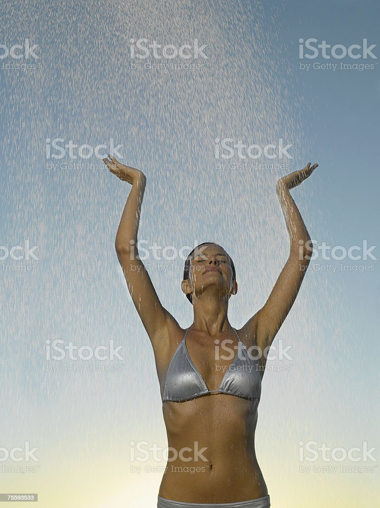 Woman in a bikini getting showered by water royalty-free stock photo