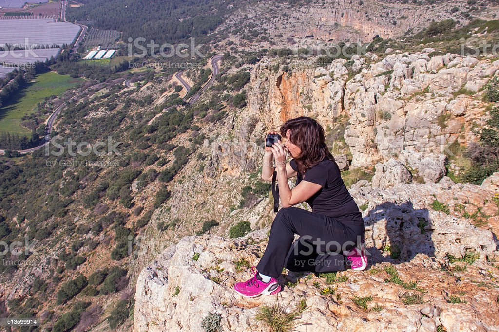 woman in a black tracksuit photographing sitting on the cliff stock photo