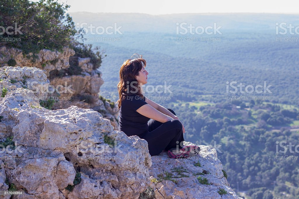 woman in a black tracksuit sitting on the cliff stock photo