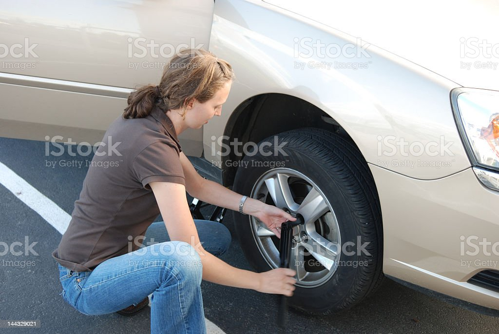 Woman in a brown shirt and jeans changing a tire royalty-free stock photo