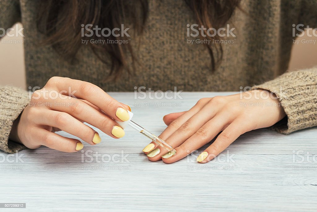 Woman in a brown sweater with yellow manicure applying cosmetic stock photo