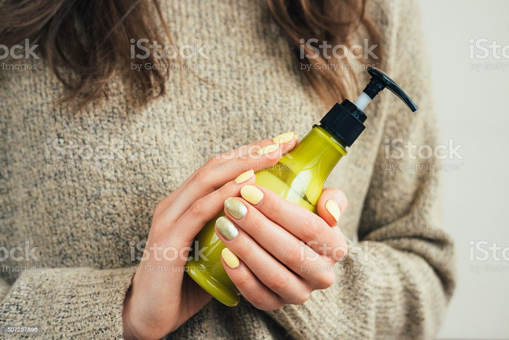 Woman in a brown sweater with yellow manicure holding bottle stock photo
