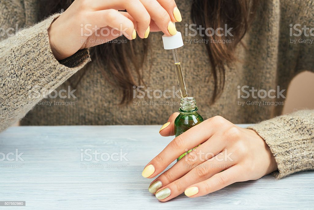 Woman in a brown sweater with yellow manicure stock photo
