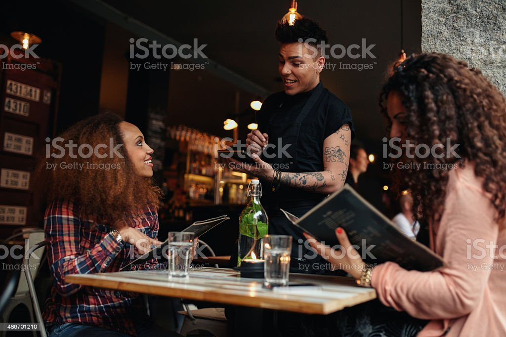 Woman in a cafe ordering to waiter stock photo