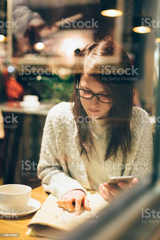 Woman in a cafe searching for job in the newspaper stock photo