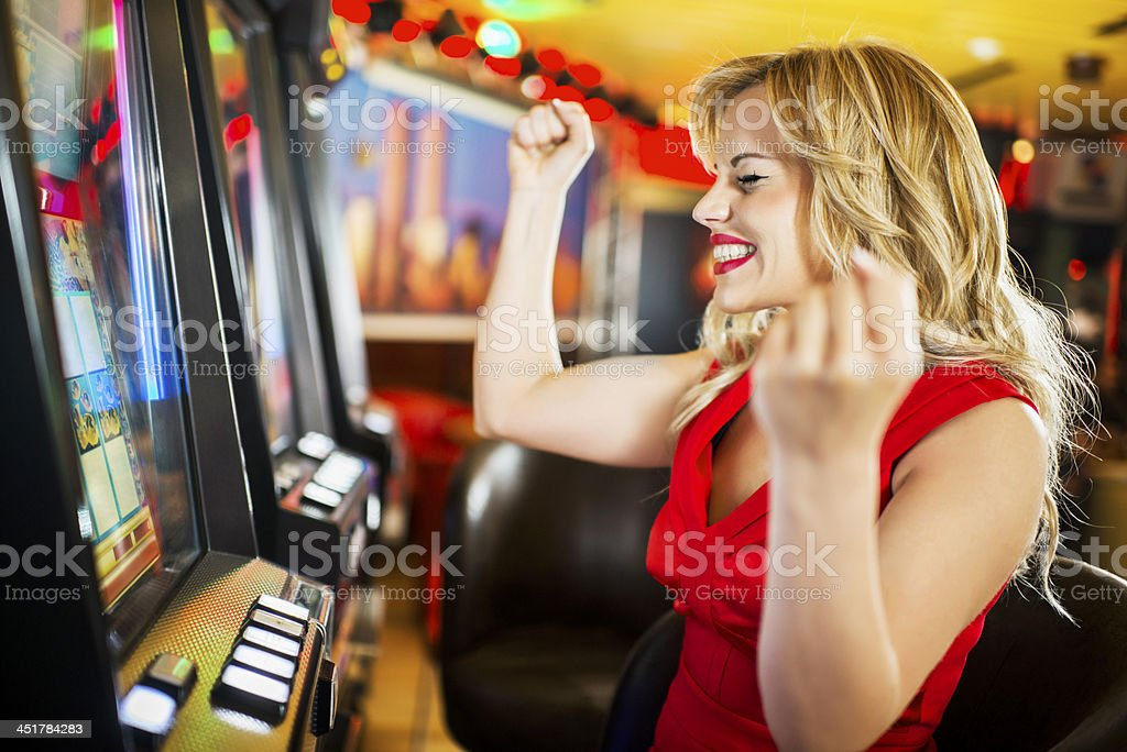 Woman in a casino winning at slot machine. stock photo