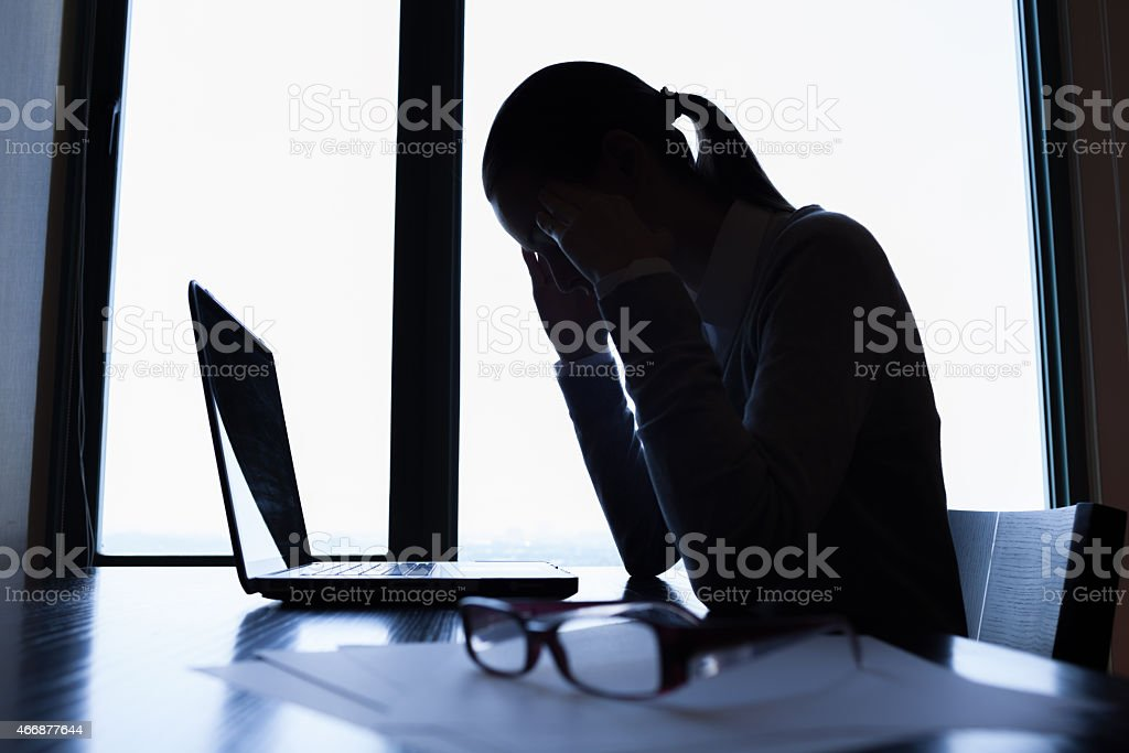 Woman in a dark room on her computer, stressed, glasses off stock photo