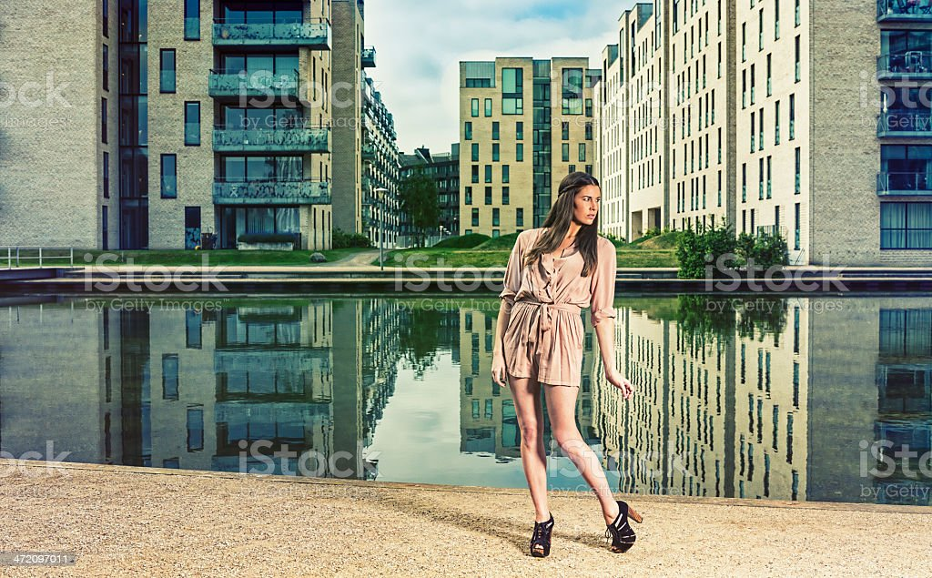 Woman in a dress is tiptoeing thorugh new residential area royalty-free stock photo