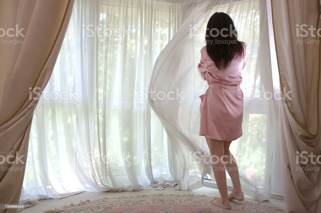 woman in a dressing gown stand at a window looks out stock photo