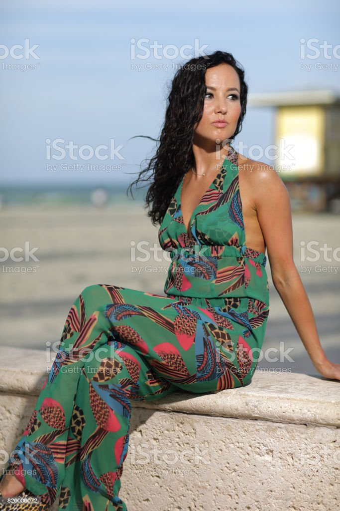 Woman in a floral print dress on the beach stock photo