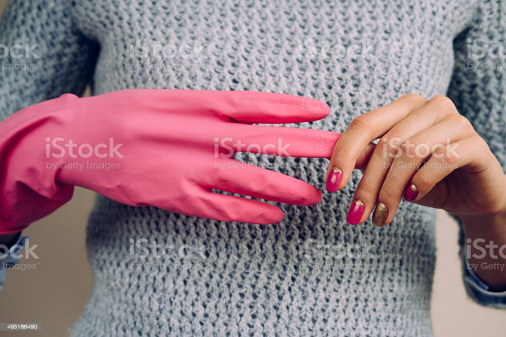Woman in a gray sweater removes pink cleaning gloves closeup stock photo