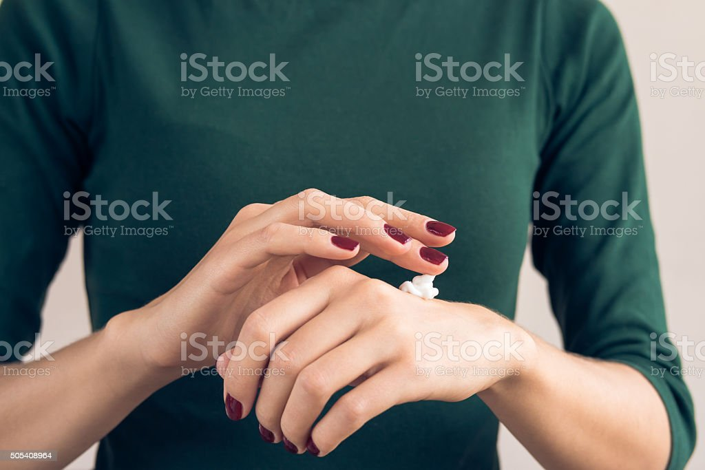 Woman in a green T-shirt and a maroon manicure stock photo