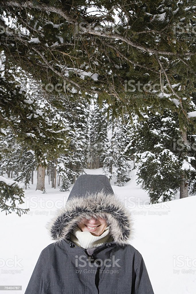 Woman in a hood by snowy trees royalty-free stock photo